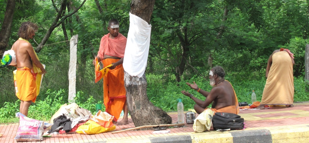 They seem to be in discussion about stacks of brightly-coloured synthetic fly-whisks, which would seem of dubious profitability so perhaps they are presents for other sadhus.