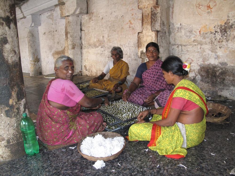 Ladies prepare thousands of tiny little oil lamps.